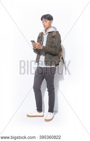 full length portrait of young man in sweatshirts with jacket and black pants and brown backpack , use a Phone   standing on white background