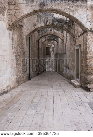 Narrow Deserted Street, Stone Walls And Arches. Monopoli, Italy.