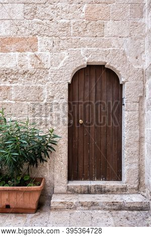 Arched Entrance To The Building. Stone Portal, Closed Wooden Door, Porch And Plants. Monopoli, Italy