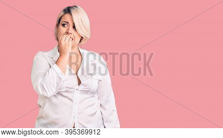 Young blonde plus size woman wearing casual shirt looking stressed and nervous with hands on mouth biting nails. anxiety problem.