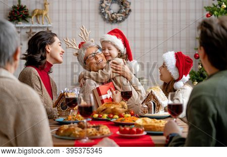 Merry Christmas! Happy family are having dinner at home. Celebration holiday and togetherness near tree.