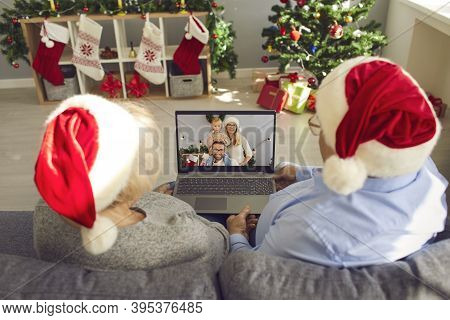 Senior Couple Grandparents In Christmas Festive Hats Sitting On Sofa And Chatting With Family Online