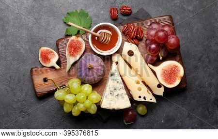 Antipasto plate with cheese, figs and grapes. Appetizer board. Top view flat lay