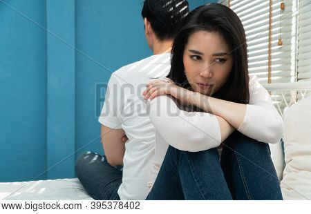Unhappy Couples Sitting Behind Each Other On The Bed And Avoid Talking Or Looking At Each Other, Cau