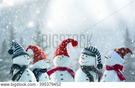 Merry Christmas and happy New Year greeting card with copy-space.Many snowmen standing in  Christmas landscape.Winter background