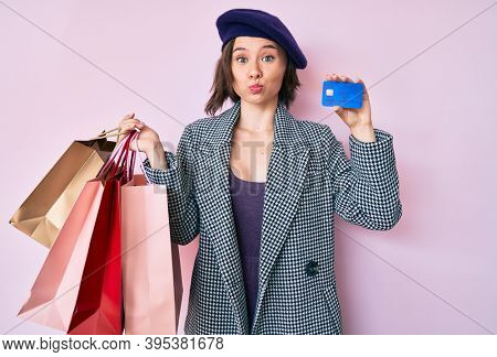 Young beautiful woman wearing beret holding shopping bags and credit card puffing cheeks with funny face. mouth inflated with air, catching air.