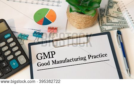 Paper With Gmp Good Manufacturing Practice On The Office Table, Calculator And Money