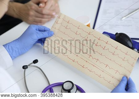 Doctors Hands Hold Result Of The Cardiogram Next To Patient Sitting. Examination Of The Cardiovascul