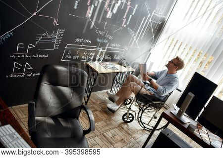 Happy Young Male Trader In A Wheelchair Holding Some Documents And Looking At Charts And Graphs On B