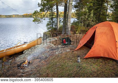 Campsite With Orange Tent On Northern Minnesota Lake During An Autumn Morning