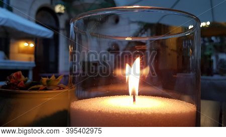 Transparent Glass Candle Holder With Flame Inside. Burning Fire Of Candle On Table. Blurred Reflecti