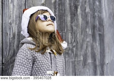 Cool Little Girl Wearing Santa Claus Hat And Sunglasses Standing Against  A Wooden Grunge Background