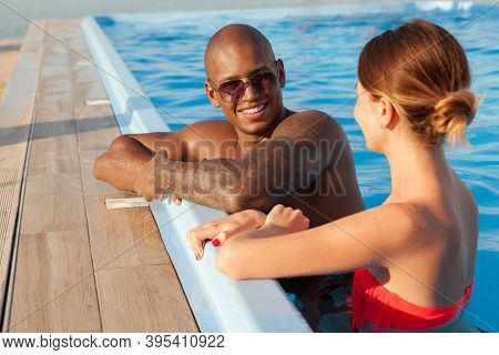 Attractive Cheerful African Man Talking To His Girlfriend At The Swimming Pool. Multiethnic Couple E