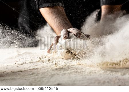 Powdery Flour Flying Into Air. Chef Hands With Flour In A Freeze Motion Of A Cloud Of Flour Midair.