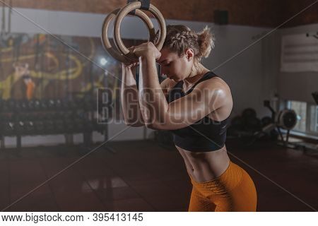 Stunning Female  Athlete Resting After Exercising On Gymnastic Rings At The Gym, Copy Space.