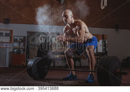 Muscular Shirtless Mature Man Chalking Hands Before Weightlifting, Copy Space. Ripped Strong Crossfi