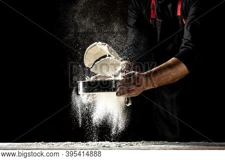The Chef Sprinkles Flour Through A Sieve, Powdery Flour Flying Into Air. Chef Hands With Flour In A