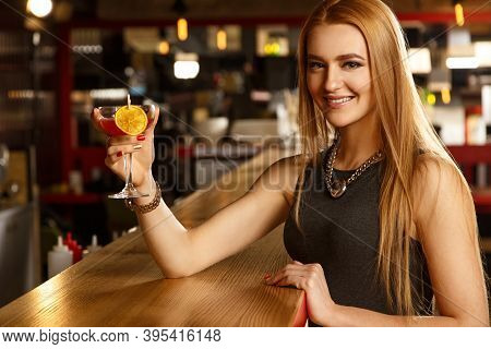 Raise Your Glass. Portrait Of A Beautiful Cheerful Young Woman Smiling To The Camera Raising Her Gla