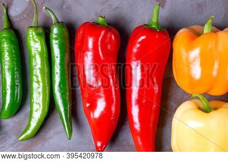 Assortment Of Peppers On The Grey Table. Top View. Multicolored Harvest Of Homegrown Vegetable