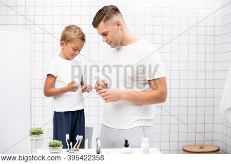 Father Looking At Son Holding Dental Floss While Standing Near Washbasin With Toiletries In Bathroom