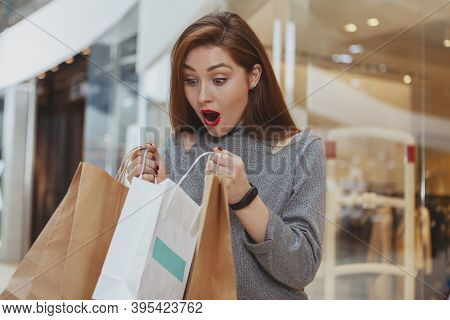Beautiful Overwhelmed Woman Looking Inside A Shopping Bag At The Mall. Attractive Female Cusotmer Lo