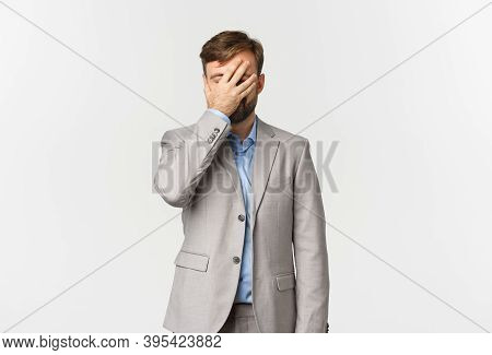 Portrait Of Tired And Annoyed Bearded Businessman In Grey Suit, Facepalming, Slap His Face And Stand