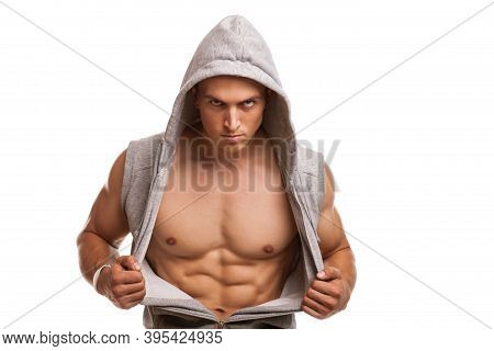Fierce Muscular Man Opening His Hoodie, Showing Off Ripped Body, Looking To The Camera. Young Athlet