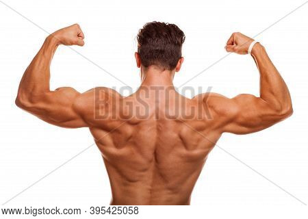 Rear View Shot Of A Male Bodybuilder Showing Off His Muscles, Flexing Biceps And Back Isolated. Athl