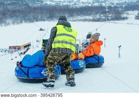 Lviv, Ukraine - January 7, 2019: Winter Fun Activities. Ride Down By Hill On Snow Tubing