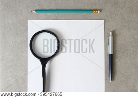 Template Of White Paper With A Ballpoint Pen, Magnifying Glass And Simple Pencil On Light Grey Concr