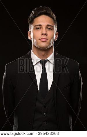 Vertical Studio Portrait Of A Handsome Young Secret Service Agent Wearing Black Suit And A Tie Posin
