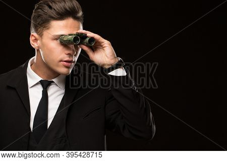 Close Up Shot Of A Handsome Professional Secret Service Agent Looking Away Using Binoculars On Black