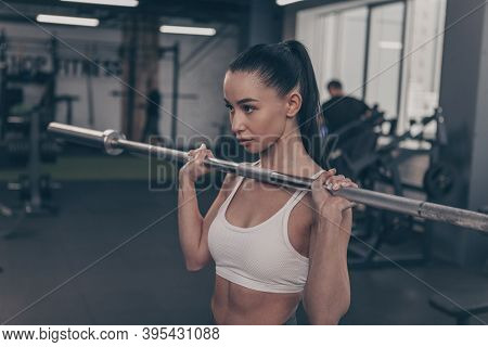 Gorgeous Fit And Toned Sportswoman Lifting Barbell At The Gym, Copy Space On The Side. Attractive Fe