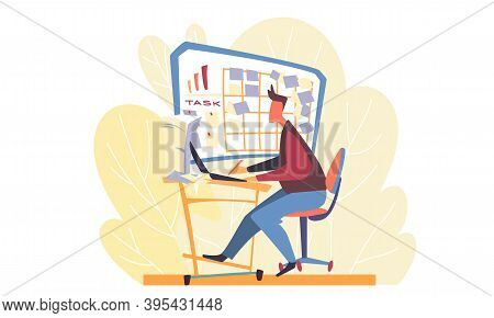 A Man Working At A Laptop And Looking At A Board With Stickers And Assignments Over His Desk. The Ba