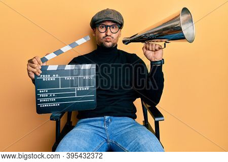 Handsome man with tattoos holding video film clapboard and louder puffing cheeks with funny face. mouth inflated with air, catching air.