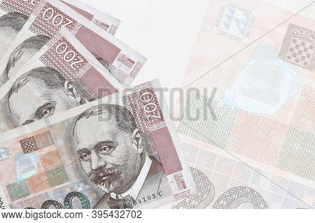 200 Croatian Kuna Bills Lies In Stack On Background Of Big Semi-transparent Banknote. Abstract Busin