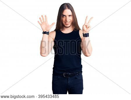 Young adult man with long hair wearing goth style with black clothes showing and pointing up with fingers number seven while smiling confident and happy.