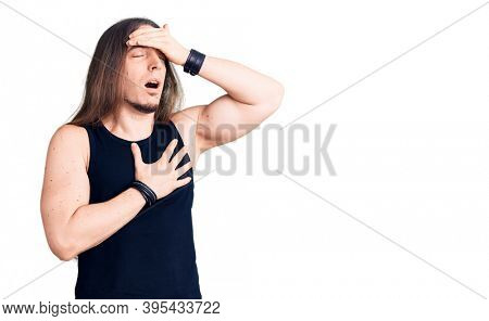 Young adult man with long hair wearing goth style with black clothes touching forehead for illness and fever, flu and cold, virus sick