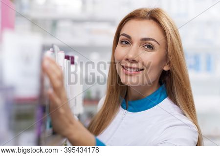 Close Up Of A Cheerful Drugstore Worker Smiling To The Camera, While Checking Stock. Happy Beautiful