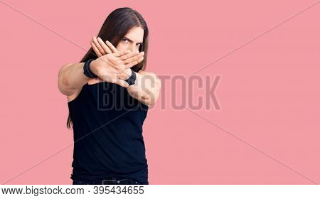 Young adult man with long hair wearing goth style with black clothes rejection expression crossing arms and palms doing negative sign, angry face