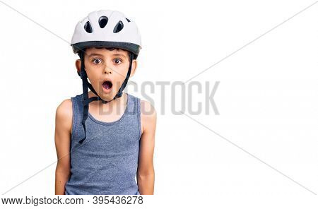 Little cute boy kid wearing bike helmet scared and amazed with open mouth for surprise, disbelief face