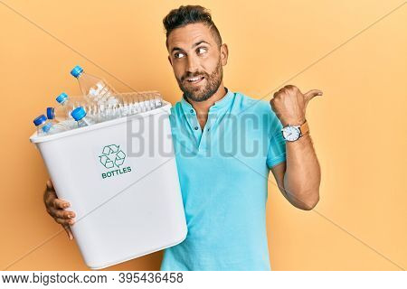 Handsome man with beard holding recycling wastebasket with plastic bottles pointing thumb up to the side smiling happy with open mouth