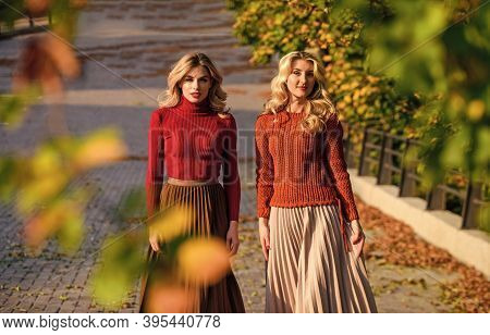 Fall Fashion. Pleated Skirt Fashion Trend. Women Walking In Autumn Park. Friends Girls. Autumn Styli