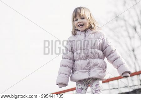 Smiling Cute Little Girl In Warm Jacket Or Warm Clothing At Winter.