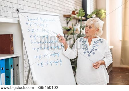 Senior Female Teacher Writes Algebra Formulas On A Whiteboard And Explains In Modern Classroom