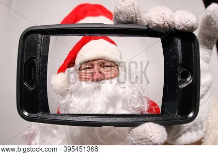Santa Claus. Santa smiles as he looks into his cell phone for fun and funny Christmas Photos. Santa Claus loves all people and Christmas. Merry Christmas to all. Ho Ho Ho.
