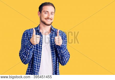 Young handsome caucasian man wearing casual clothes success sign doing positive gesture with hand, thumbs up smiling and happy. cheerful expression and winner gesture.