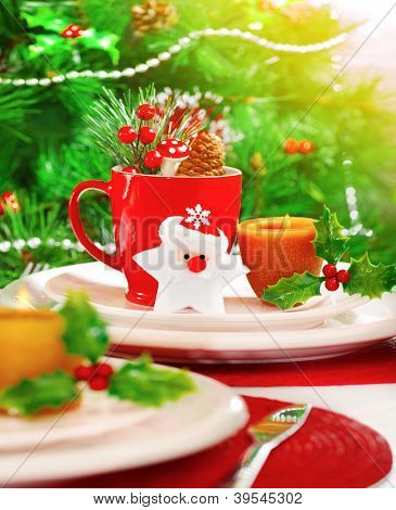 Picture of Christmas eve table setting with beautiful holiday decorations, white and red festive utensil, warm yellow candle light, Santa Claus star toy, little berry branch, New Year party
