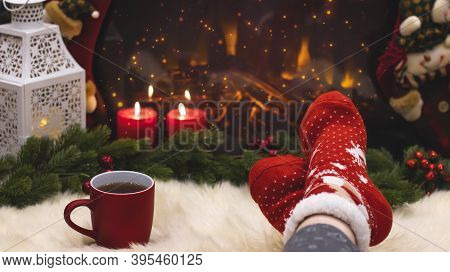 Red Knitted Socks Against The Background Of New Year's Decorations And Fireplace, Christmas Tree Gar