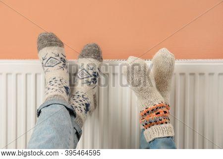 Couple Warming Legs On Heating Radiator Near Color Wall, Closeup